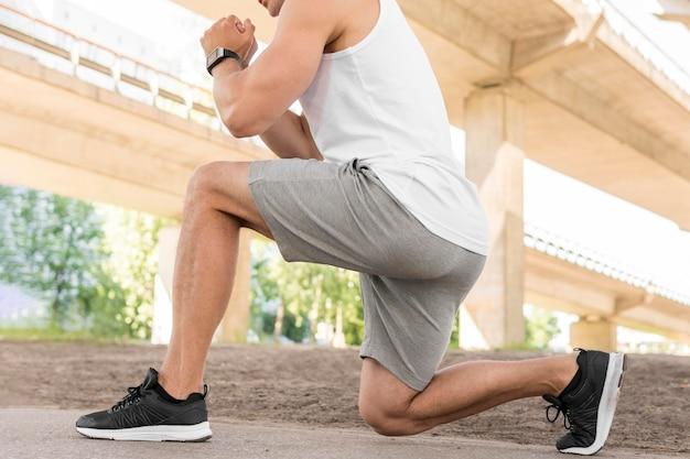 Vista lateral atlético hombre estirando fuera