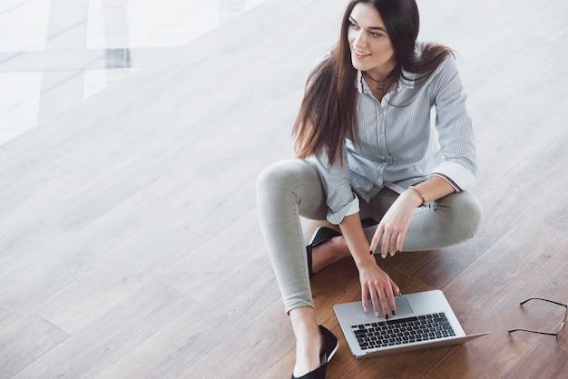 Vista lateral de la atractiva chica usando una computadora portátil en el área wifi pública y sonriendo mientras está sentado en el piso