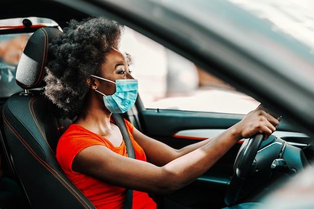 Vista lateral de la atractiva mujer africana con pelo corto y rizado con mascarilla al sentarse y conducir un coche. prevención de la propagación del concepto del virus corona / covid 19.