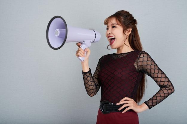 Vista lateral de la atractiva mujer gritando por megáfono con su brazo en la cintura