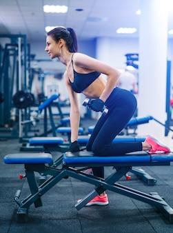 Vista lateral de la atractiva mujer que trabaja en el gimnasio con pesas en un simulador.