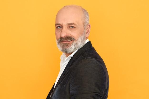 Vista lateral del atractivo caballero senior con cabeza calva y barba gris posando aislado vistiendo chaqueta negra y camisa blanca, con mirada segura, sonriendo
