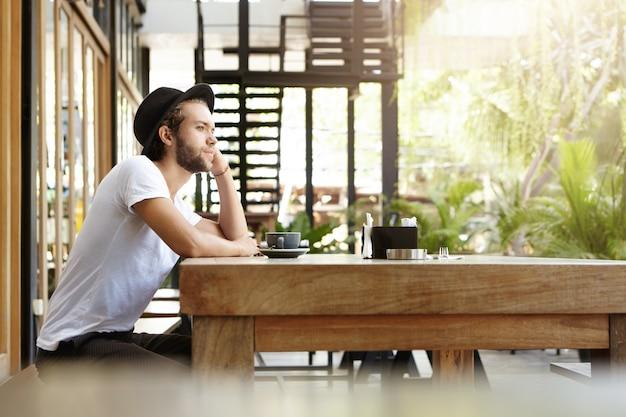 Vista lateral del atractivo joven inconformista con sombrero sentado solo en la cafetería del pavimento, apoyando el codo en la enorme mesa de madera