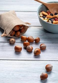 Vista lateral de avellanas esparcidas de un saco y un tazón con nueces se mezclan en madera rústica
