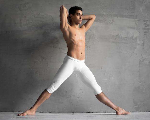 Vista lateral del bailarín de ballet masculino sin camisa posando