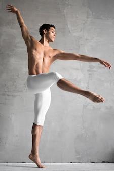 Vista lateral del bailarín de ballet masculino sin camisa