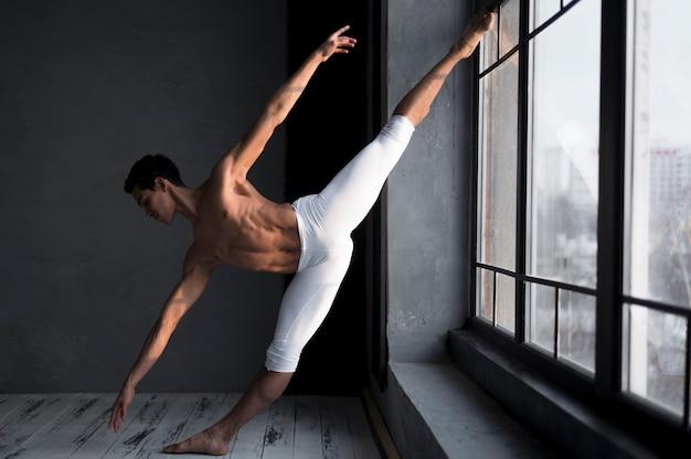 Vista lateral del bailarín de ballet masculino en medias
