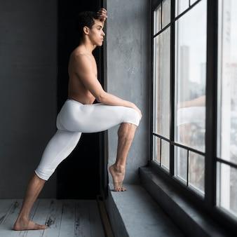 Vista lateral del bailarín de ballet masculino posando junto a la ventana