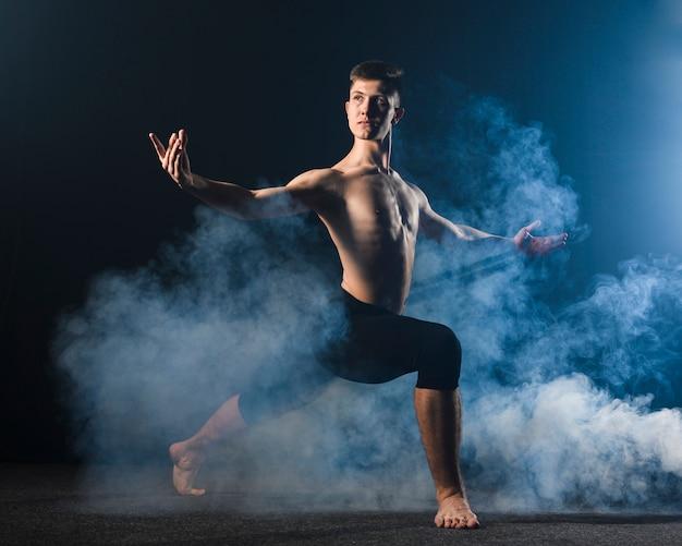 Vista lateral del bailarín en medias posando en humo