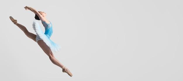 Vista lateral de la bailarina en el aire con espacio de copia