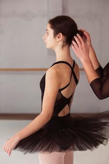 Vista lateral de la bailarina arreglando su moño de pelo