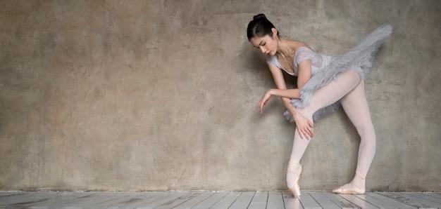 Vista lateral de la bailarina bailando en traje de tutú con espacio de copia