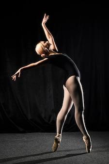 Vista lateral de la bailarina de ballet en leotardo