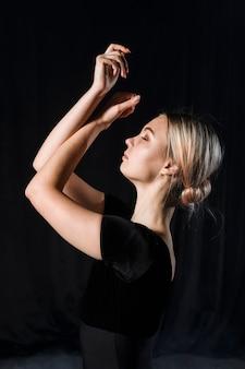 Vista lateral de la bailarina posando con los brazos