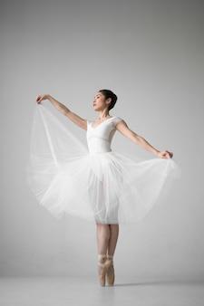 Vista lateral de la bailarina posando en traje de tutú