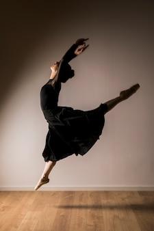 Vista lateral de la bailarina saltando postura.