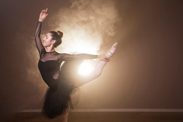 Vista lateral bailarina sonriente realizando