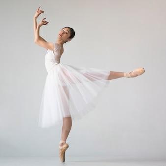 Vista lateral de la bailarina en traje de tutú posando