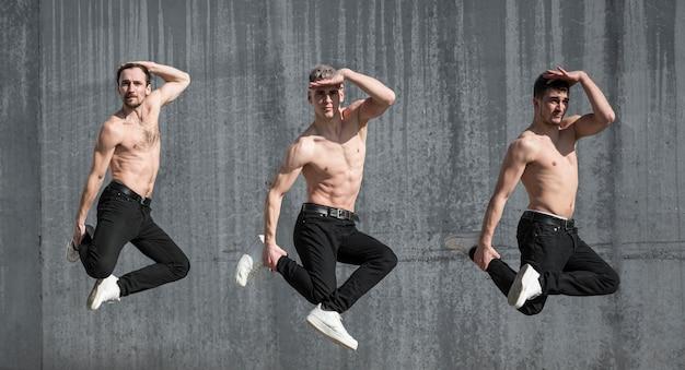 Vista lateral de bailarines de hip hop sin camisa posando mientras baila