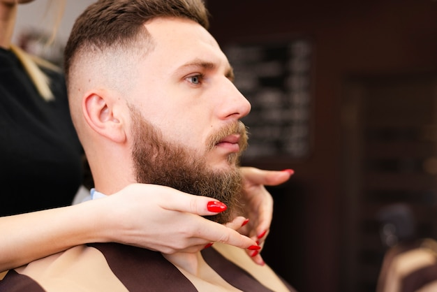 Vista lateral de la barbería trabajadora haciendo su trabajo