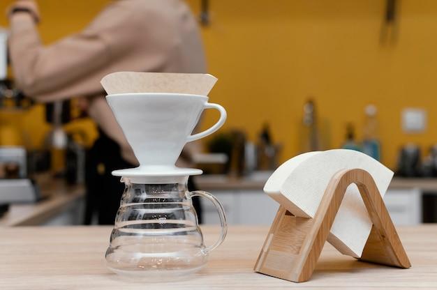 Vista lateral del barista femenino desenfocado con máscara trabajando en la cafetería