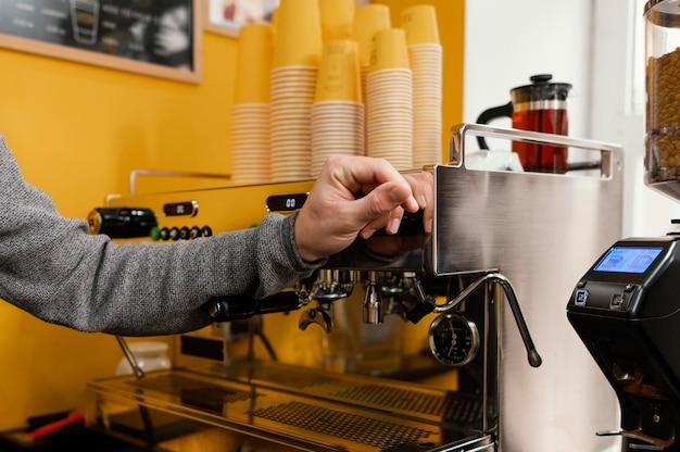 Vista lateral del barista masculino en la cafetería junto al molinillo de café