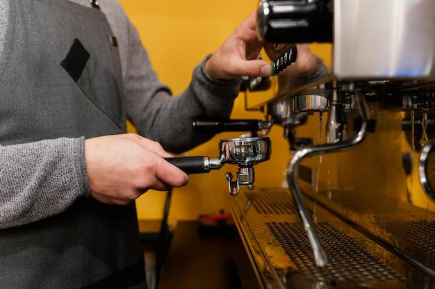 Vista lateral del barista masculino con delantal con máquina de café profesional