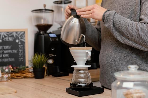 Vista lateral del barista masculino haciendo café