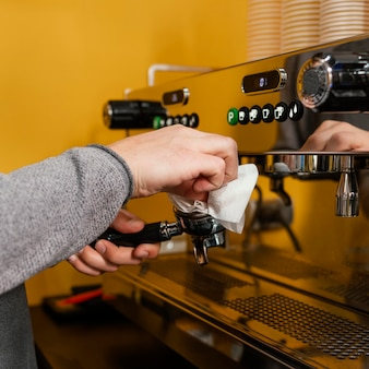 Vista lateral del barista masculino máquina de café profesional de limpieza