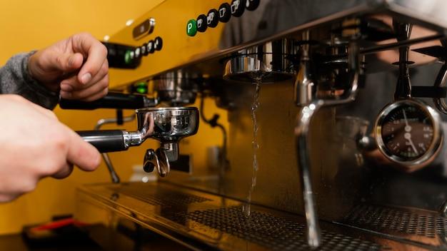 Vista lateral del barista masculino con máquina de café profesional