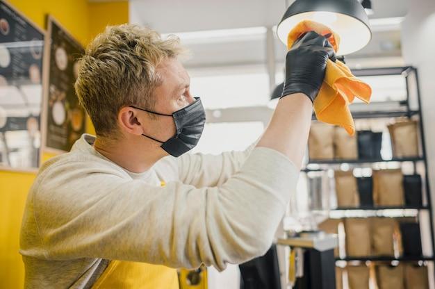 Vista lateral del barista masculino con máscara médica lámparas de limpieza en la cafetería.
