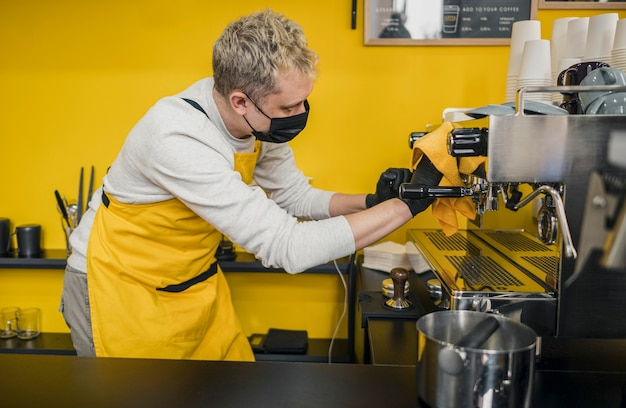 Vista lateral del barista masculino con máscara médica máquina de café de limpieza