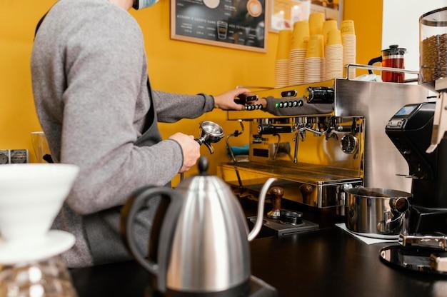 Vista lateral del barista masculino trabajando en la cafetería.