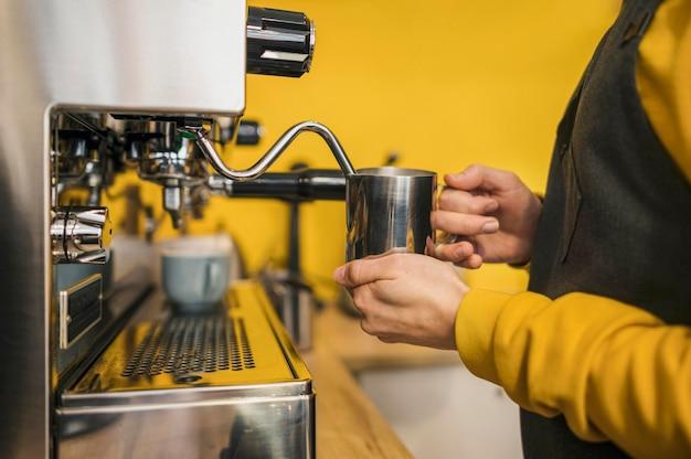 Vista lateral del barista usando una máquina para espumar leche
