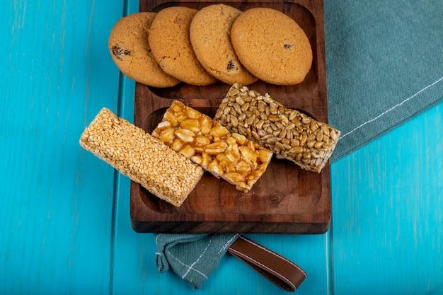 Vista lateral de barras de miel con semillas de maní, sésamo y girasol con galletas de avena en una tabla de madera