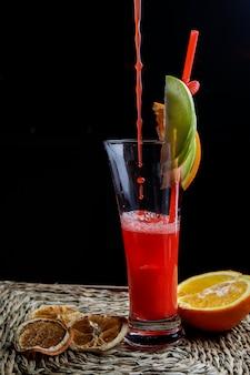 Vista lateral batido de frutas rojas con túbulos para bebidas y limón seco y gotas en servilletas
