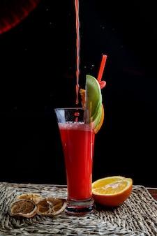 Vista lateral batido de frutas rojas con túbulos para bebidas y media naranja y gotas en servilletas