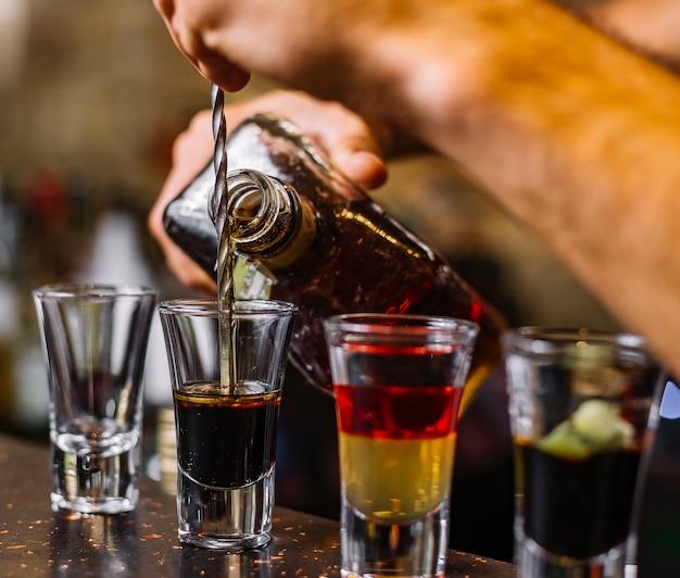 Vista lateral de bebidas alcohólicas multicolores licor con una rodaja de kiwi sobre la mesa