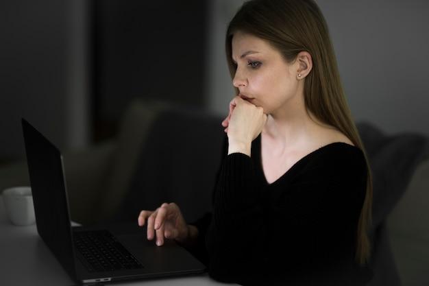 Vista lateral de la bella mujer que trabaja en el escritorio