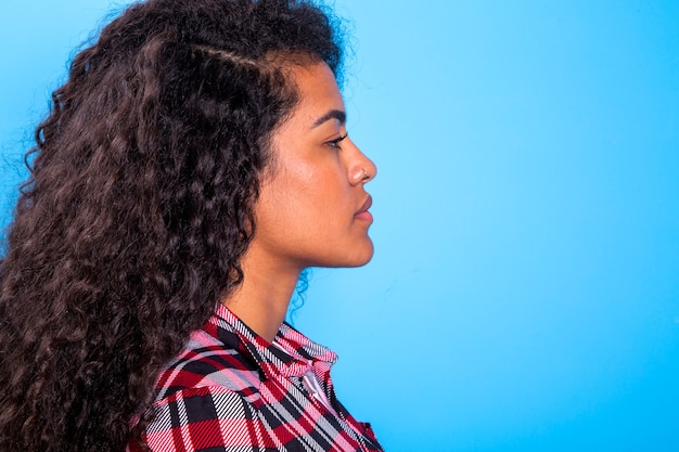 Vista lateral de la belleza de la mujer bastante africana sobre fondo azul - imagem.