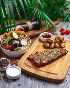 Vista lateral de bistec con ensalada de carne roja a la parrilla con pepino, tomate, rábano, lechuga y papas asadas sobre la mesa