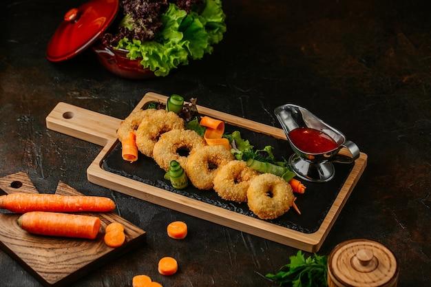 Vista lateral bocadillos aros de cebolla palitos de mozzarella papas fritas y salsas en una placa