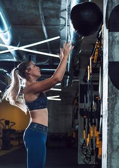 Vista lateral de una bola de medicina que lanza de la mujer atlética en gimnasio