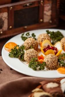Vista lateral de bolas de semillas de sésamo con hierbas decorativas, zanahorias y rodajas de mandarina