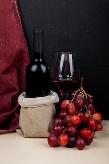 Vista lateral de la botella y vaso de vino tinto con uva y tela sobre superficie blanca y fondo negro