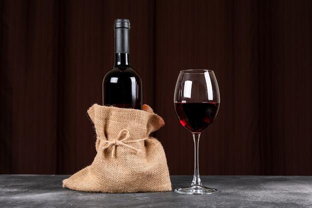 Vista lateral botella de vino tinto en bolsa de tela de saco en la mesa oscura y horizontal