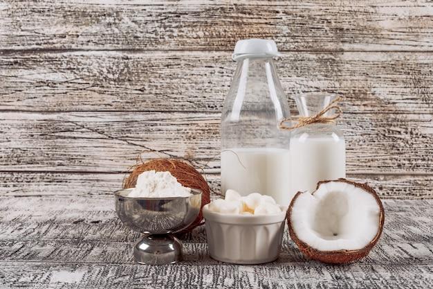 Vista lateral botellas de leche con dividido en la mitad de cocos, queso y harina sobre fondo de madera gris. horizontal