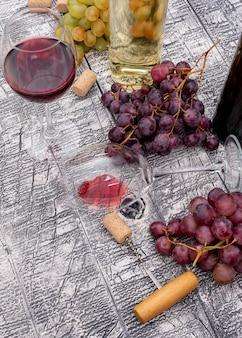 Vista lateral de botellas de vino con uva en vertical de madera blanca