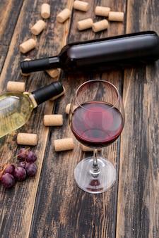 Vista lateral de botellas de vino con vidrio en madera oscura vertical