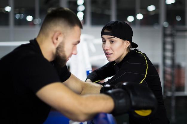 Vista lateral del boxeador y el entrenador teniendo una conversación